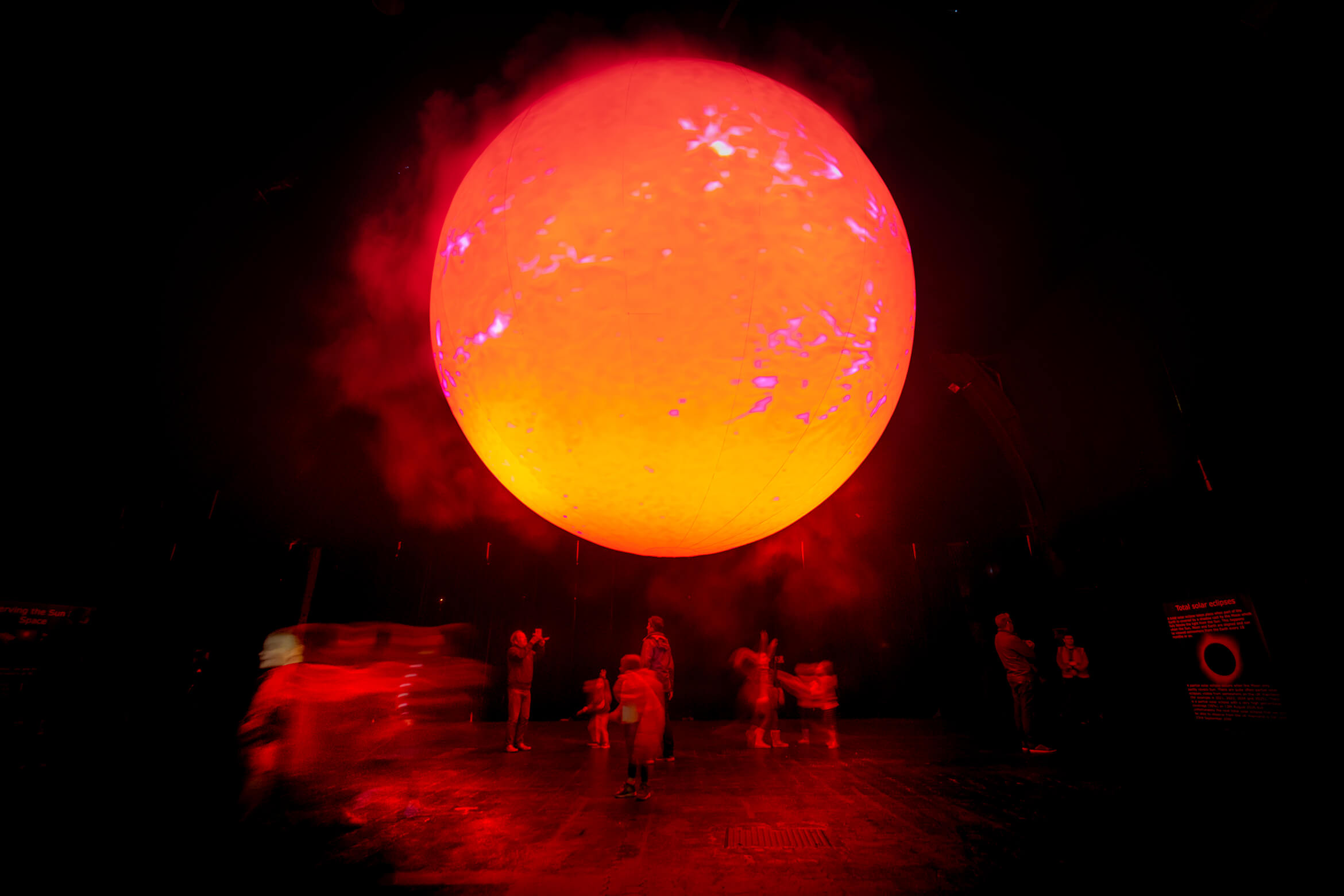 Photograph of SUN showing in a red phase with people below